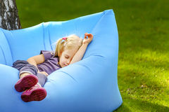 Young cute blond girl sleeping on an inflatable bed outdoors Royalty Free Stock Image