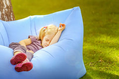 Young cute blond girl sleeping on an inflatable bed outdoors Stock Image