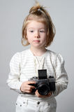 Young, cute, blonde girl holding vintage camera in the studio Royalty Free Stock Photo