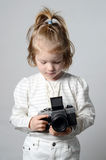Young, cute, blonde girl holding vintage camera in the studio Stock Photo