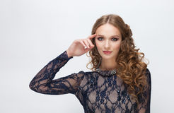 Young cute blonde woman with curly hairstyle in blue dress and necklace touching her face by fingers posing on white studio backgr Royalty Free Stock Photography
