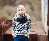 Young cute blonde woman in sweater, scarf, and jeans outdoors portrait with abandoned grunge background Royalty Free Stock Photography
