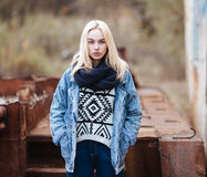 Young cute blonde woman in sweater, scarf, and jeans outdoors portrait with abandoned grunge background Stock Photos