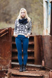 Young cute blonde woman in sweater, scarf, and jeans outdoors portrait with abandoned grunge background Royalty Free Stock Images