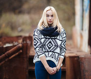 Young cute blonde woman in sweater, scarf, and jeans outdoors portrait with abandoned grunge background Royalty Free Stock Image