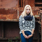 Young cute blonde woman in sweater, scarf, and jeans outdoors portrait with abandoned grunge background Royalty Free Stock Photos