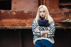 Young cute blonde woman in sweater, scarf, and jeans outdoors portrait with abandoned grunge background Stock Photo
