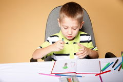 Young cute boy draws with color pencils Royalty Free Stock Photo