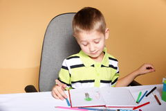 Young cute boy draws with color pencils Royalty Free Stock Photography