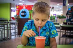 Young cute boy drink fruit juice in cafe Stock Images