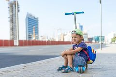 Young cute boy is sitting on the Kick scooter at a bus stop near the Emirates Mall in Dubai, waiting for the bus. United Arab Emir. Ates, road to the beach Stock Photography