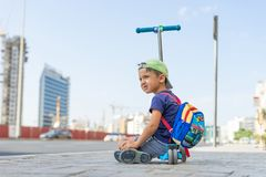 Young cute boy is sitting on the Kick scooter at a bus stop near the Emirates Mall in Dubai, waiting for the bus. United Arab Emir. Ates, road to the beach Stock Photos