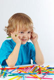 Young cute boy at the table with color pencils Stock Images