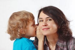 Young cute boy whispers secrets to his mother. On a white background Stock Photography