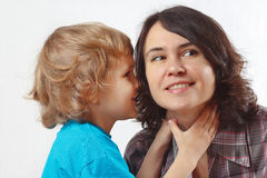 Young cute boy whispers something to his mother. On a white background Royalty Free Stock Image