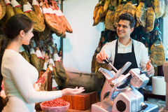 Young cute brunette choosing iberico and serrano jamon. And smiling Royalty Free Stock Photo