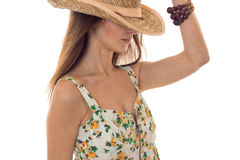 Young cute brunette girl in sarafan with floral pattern and straw hat with wide brim posing with hide eyes isolated on. White royalty free stock photo