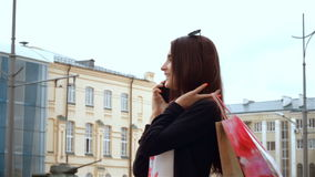 Young cute brunette girlfriend calls and keeps the shoulder bags. From stores stock video footage
