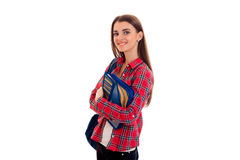 Young cute brunette student woman with blue backpack on her shoulder and folder for notebooks in hands looking at the Royalty Free Stock Images