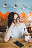 Woman drinks milkshake beautifully decorated with cream and cookies stock images