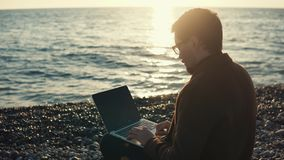 Adult man working on a laptop computer, businessman sitting by the sea. Young and cute businessman working near the sea during his autumn vacation, busy man stock footage