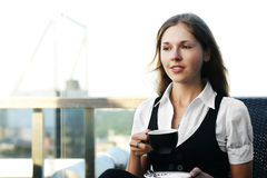 A young and cute businesswoman is drinking coffee Stock Photo