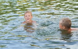 Young cute boy and his little brother playing in the water in a beautiful river or lake on a sunny summer day stock photos