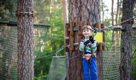 Young cute child boy in summer clothing, safety harness and helmet attached with carbine to cable moves slowly along rope way on stock photo