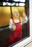 Young cute child standing at window Royalty Free Stock Images