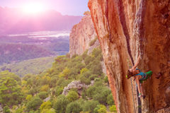 Young cute Climber Hanging on one hand on rocky Wall Stock Photo