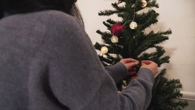 Young cute couple decorating the Christmas tree in the room before holiday. New Year and Christmas time concept. Happy. Young positive couple decorating the stock footage