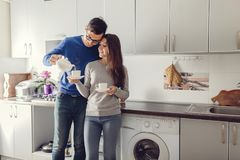 Young cute couple hugging and drinking tea in the kitchen. stock image