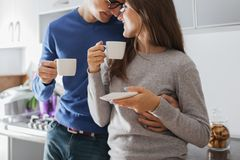 Young cute couple hugging and drinking tea in the kitchen royalty free stock photography