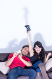 Young cute couple playing video games. Having fun in livingroom Royalty Free Stock Images