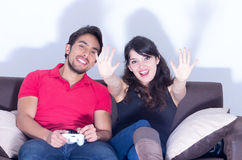 Young cute couple playing video games. Having fun in livingroom Royalty Free Stock Photos