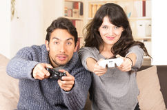 Young cute couple playing video games. Looking at camera in livingroom Stock Image