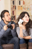 Young cute couple playing video games. Young cute playful couple playing video games in livingroom Royalty Free Stock Photos