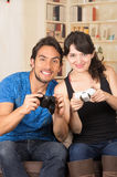 Young cute couple playing video games. Young cute smiling couple playing video games in livingroom Stock Photos