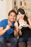 Young cute couple playing video games. Young cute smiling couple playing video games in livingroom Royalty Free Stock Photography