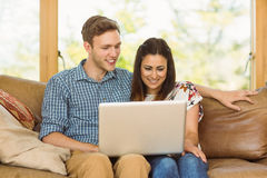 Young cute couple relaxing on couch with laptop Stock Photo