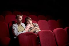 Young couple sitting at red movie theatre royalty free stock image