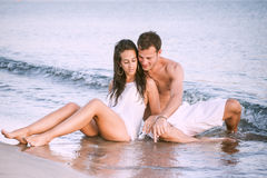 Young cute couple sitting in shallow water together. Cute couple sitting in shallow water together flirting royalty free stock photo
