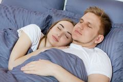Young cute couple sleeping together in bed. Comfortable bed and mattress.  royalty free stock photos