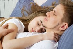 Young cute couple sleeping together in bed. Comfortable bed and mattress.  royalty free stock image