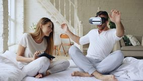 Young cute couple with tablet computer and virtual reality headset playing 360 VR video game while sitting in bed at. Home. Woman control her boyfriend stock photos
