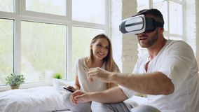 Young cute couple with tablet computer and virtual reality headset playing 360 VR video game while sitting in bed at. Home. Woman control her boyfriend stock image