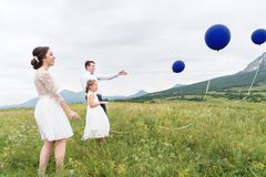 A young couple and their daughter in wedding dresses are walking in nature with balloons royalty free stock photo