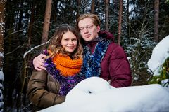 Young cute couple in a tinsel at a winter forest royalty free stock photo