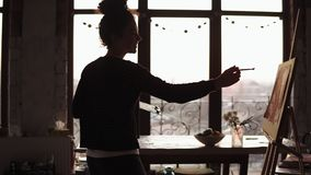 Young cute curly female artist dancing in the art studio then finishes up the lines on her painting, with the background
