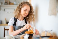 Young cute curly girl preparing breakfast for parents and smiling. royalty free stock photos